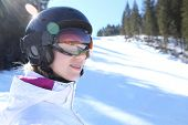 Woman wearing a helmet and glasses on the background of snow winter and mounts.