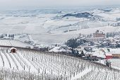 Small town of Barolo and vineyards on hills covered with snow in Piedmont, Northern Italy.