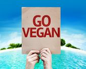 Go Vegan card with a beach on background