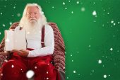 Father christmas showing a book against red background