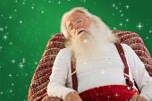 Father christmas sleeps on the armchair against red background