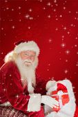 Father christmas taking red gift in his bag against red background