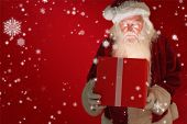 Father christmas opening a magical christmas gift against red background