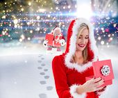 Festive blonde opening a gift against santa delivering gifts in city