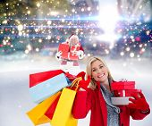 Festive blonde holding many gifts against santa delivering gifts in city