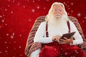Smiling santa using tablet on the armchair against red background
