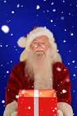 Father christmas offering a magical christmas gift against red background