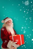Father christmas holding a gift against red background