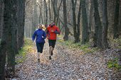 Young Couple Running on the Trail in the Wild Forest. Active Lifestyle
