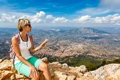 Young Woman And Panoramic View From The Mountains