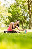 Happy fit brunette stretching on the grass in the park