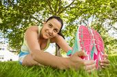 Smiling brunette in sportswear stretching on the grass in the park