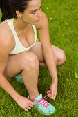Focused fit brunette tying her shoelace on the grass