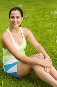 Happy fit brunette sitting on the grass in the park