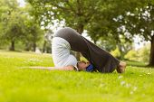 Brown hair doing yoga on grass in the park
