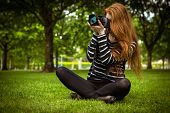Female photographer sitting on grass at the park