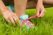 Fit woman tying her shoelace on the grass
