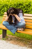 Brunette sitting on bench holding her head in the park