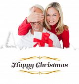 Smiling woman covering partners eyes and holding gift against border