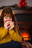 Beauty redhead drinking hot drink at christmas at home in the living room