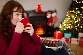 Pretty redhead drinking hot drink at christmas at home in the living room