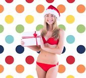 Festive fit blonde in red bikini showing gift against colorful polka dot pattern