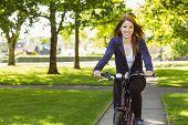 Pretty redhead cycling a bike on a sunny day