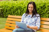Happy brunette sitting on bench using tablet in the park