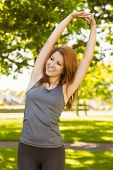 Pretty redhead stretching in the park on a sunny day