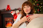 Pretty redhead holding a mug of hot chocolate at christmas at christmas at home in the living room
