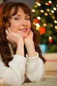 Smiling woman is resting her head on her hands at christmas at home in the living room