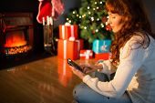 Smiling redhead using smartphone at christmas at home in the living room