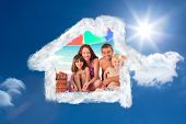 Family posing under a beach umbrella on the beach against bright blue sky with clouds