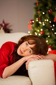 Beautiful redhead relaxing on the couch at christmas at home in the living room