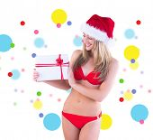 Festive fit blonde in red bikini showing gift against dot pattern