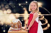 Festive little girl making gingerbread house against christmas light design
