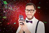Geeky hipster holding a retro cellphone against white fireworks exploding on black background