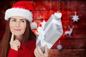 Redhead holding gift against blurred christmas background