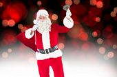 Santa claus holding a sack and bell against red glowing dots on black