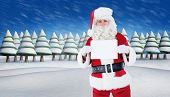 Smiling santa claus holding page against snowy landscape with fir trees