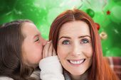 Mother and daughter telling secrets against blurred christmas background