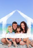 Portrait of a family at the beach against house outline in clouds