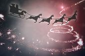 Silhouette of santa claus and reindeer against christmas light design