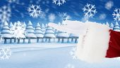 Santa claus with hand out against snowy landscape with fir trees