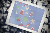 Christmas graphics against tablet pc with blue screen