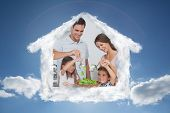 Family mixing a salad together against cloudy sky with sunshine