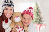 Mother and daughter with teddy against blurry christmas tree in room