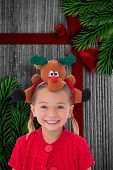 foto of rudolph  - Cute little girl wearing rudolph headband against wood with festive bow - JPG