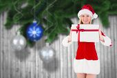 Festive blonde holding a gift against christmas baubles hanging over wood