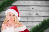 Festive blonde blowing a kiss against blurred fir branches on wood